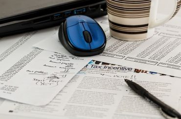 accountant's table with mouse, a mug and accounting papers