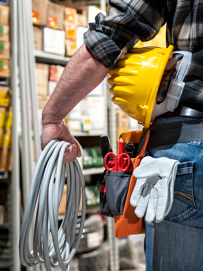 Electrician in the electrical component store